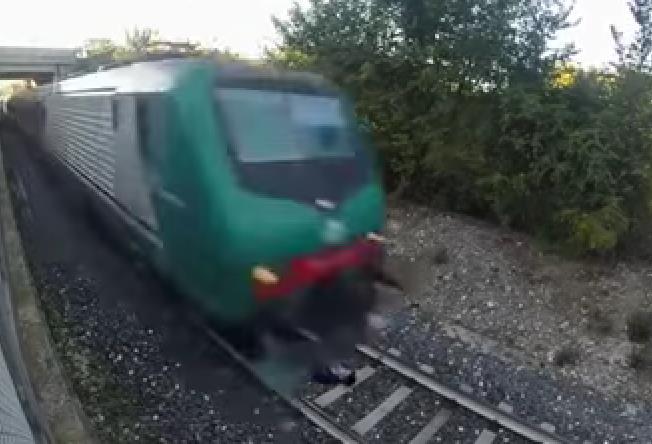 مراهق ايطالي يرقد أمام قطار سريع يمر من فوقه بسرعة فائقة .. فيديو